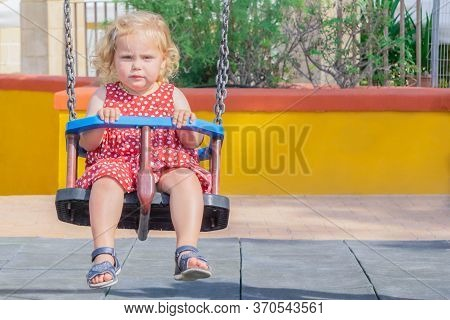 Blond Little Girl On Swings Outdoor In Playground. Toddler Swinging. Cute Girl In Red Dotted Dress S