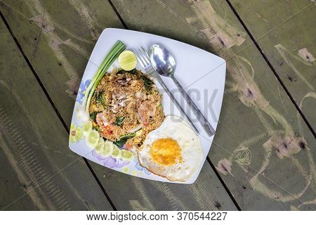 Fried Rice Seafood, Shrimp, Squid And Fried Egg On Wooden Background