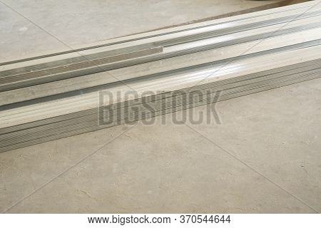 Drywall Metallic Profile On Grey Concrete Floor. Apartment Construction Concept With Copy Space
