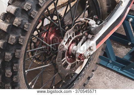 Close-up Rear Studded Wheel Of An Enduro Off-road Motorcycle In Garage On Lift. Brake Discs, Chain,