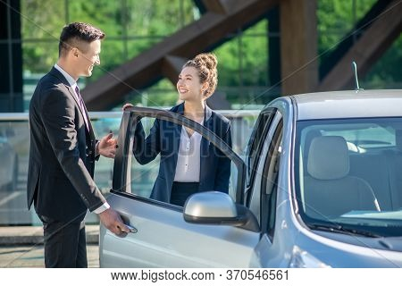 Man Opening A Car Door For A Woman.