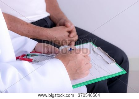 Doctor Hands With Cardiogram Chart With Pen. Cardiologist Explaining His Patient Ekg Results.