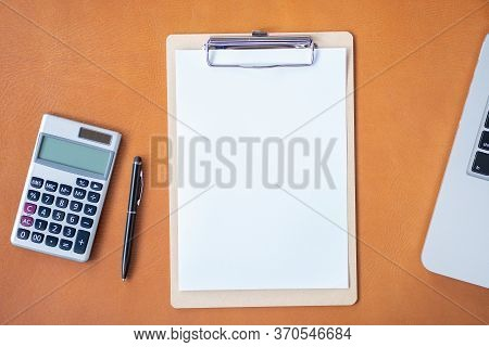 Flat Lay, Top View Office Table Desk.workspace With Calculator,pen,laptop, Empty Clipboard On Leathe