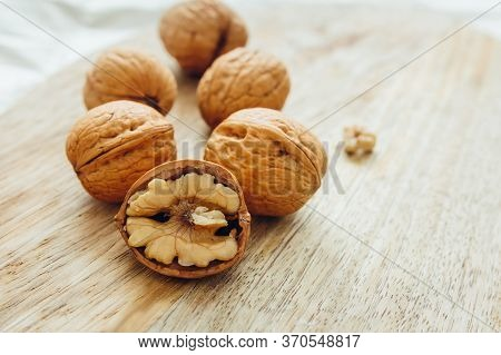 Unpeeled Walnuts On Wooden Surface, Closeup. Food Photo. Selective Focus.