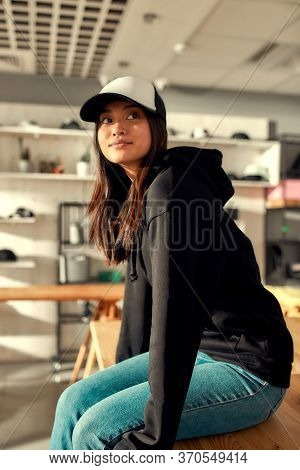 Cheerful Female Worker Looking Aside While Posing In Custom Apparel, Baseball Cap And Hoodie. Young