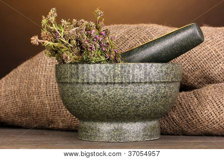Thyme herb and mortar on wooden table on brown background poster