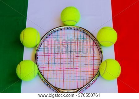 Tennis Racket In Metal With Colored Ropes And Yellow Tennis Balls With The Italian Flag In The Backg