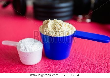 Plastic Spoon Or Measuring Scoop Of Whey Protein And Bcaa On Background Of Sports Equipment, Shaker