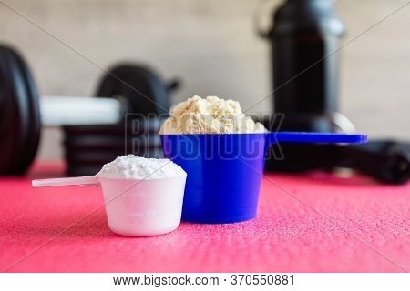 Plastic Spoon Or Measuring Scoop Of Whey Protein And Creatine On Background Of Sports Equipment, Sha