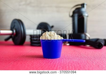 Plastic Spoon Or Measuring Scoop Of Whey Protein On The Background Of Sports Equipment, A Shaker For
