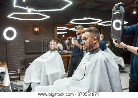 Look Here. Two Barbers Holding Mirrors And Showing Haircuts To Father And Son Sitting In Armchair At
