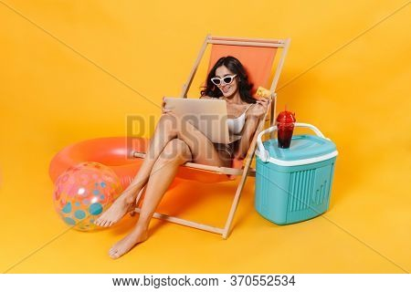 Image of happy woman using laptop and holding credit card while resting in chaise lounge isolated over yellow wall