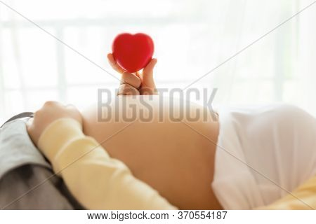 Happy Pregnant Young Woman Holding Red Heart In Hand On Top Of Mother Belly In Hospital Bed. Prenata