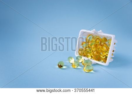 Capsules Of Omega 3 Vitamin Supplement Isolated On Blue Background With Copy Space. Fish Oil, Vitami