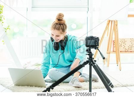 Smiling girl using laptop and dslr camera in bright room