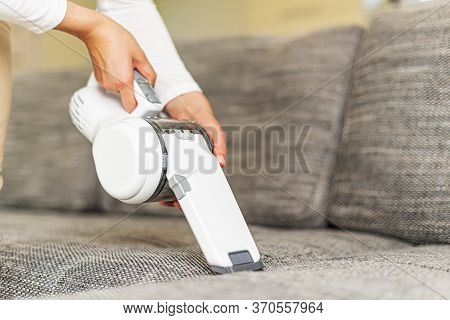 A Woman Vacuuming Furniture In A House With A Hand-held Portable Vacuum Cleaner.