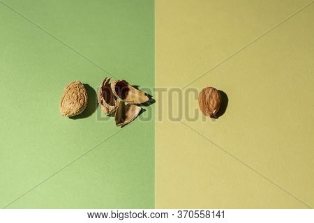 Peeled Almond Along With Its Shells And Another Almond In Shell On Green And Yellow Background