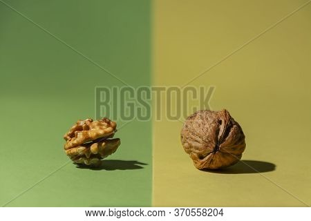 One Raw Nut From The Tree Along With Another One Without Shell On Green And Yellow Background