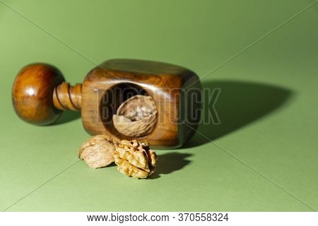 Peeled Nut Next To Its Shells And A Nutcracker, On Green Background