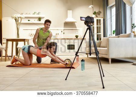 Man And Woman In Sportswear Recording Video Blog Or Vlog About Healthy Lifestyle On Camera While Exe
