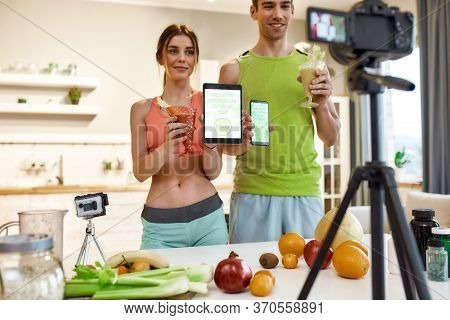Young Couple Recording Video Blog Or Vlog About Healthy Nutrition On Camera At Home. Man And Woman H