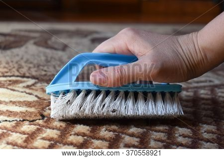 Cleaning The House With A Brush. Woman Housewife Brushes The Carpet. Manual Cleaning Of The Apartmen