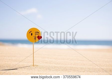 Maspalomas, Gran Canaria - October, 2019: Emoji Blowing Kiss On Stick On Sandy Beach At Sunny Day