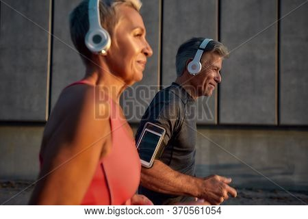 Common Sport Activities. Happy And Healthy Middle-aged Couple In Headphones Running Together Through