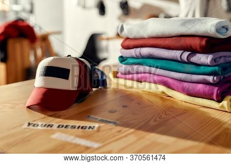 Custom Apparel, Clothes Neatly Folded On Shelves. Stack Of Colorful Clothing And Baseball Cap In The