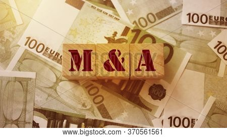 Mergers And Acquisitions, M And A Concept. Text On Wooden Cubes And Cash In 100 Euro Bills