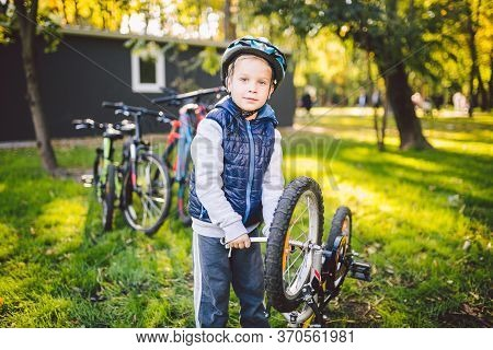 Caucasian Child Boy In A Helmet Learns To Repair His Bike. Child Cyclist Checks The Mechanism Of A B