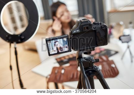 Asian Female Blogger Applying Makeup While Recording A Tutorial Video For Her Beauty Blog Using Came