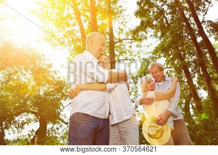 Two couples in love hug happily in the summer in the park