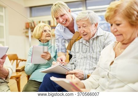 Psychotherapist helps demented seniors with group therapy in a retirement home