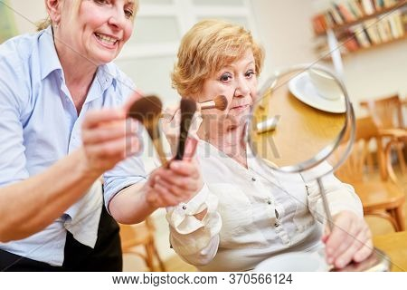 Old woman in the make-up course doing the styling in front of the mirror together with a make-up artist