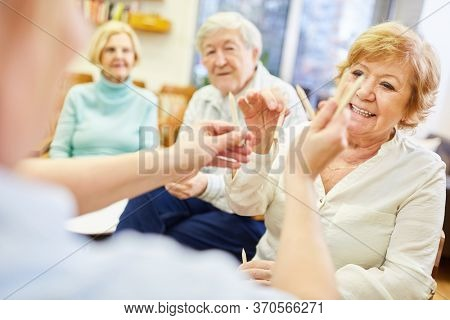 Female doctor and group of senior citizens with colored pencils in an occupational therapy