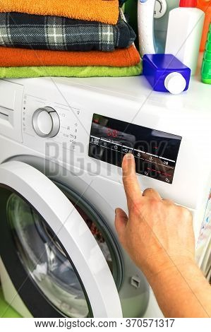 Close Up Of Man Choosing Cycle Program On Washing Machine. Adjusting Wash Settings On The Control Pa