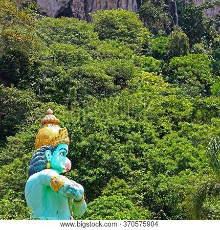 Hindu God Hanuman Against Natural Green Background. Sculpture Near Batu Caves In Kuala Lumpur, Malay