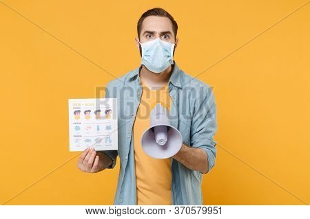 Shocked Young Man In Sterile Face Mask Isolated On Yellow Background. Epidemic Pandemic Coronavirus