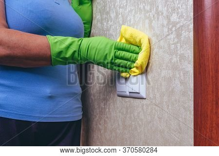 Cleaning In The House. A Girl In Green Gloves Wipes The Electricity Switch With A Yellow Cloth. Clea