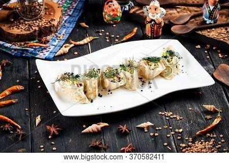 Gourmet Slapjack Rolls With Salmon Filling Black Caviar Dill Garnish On A White Plate, Horizontal