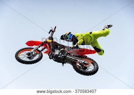 Biker In A Protective Bright Suit And Helmet Does A Stunt Jump On A Motorcycle On A Motocross
