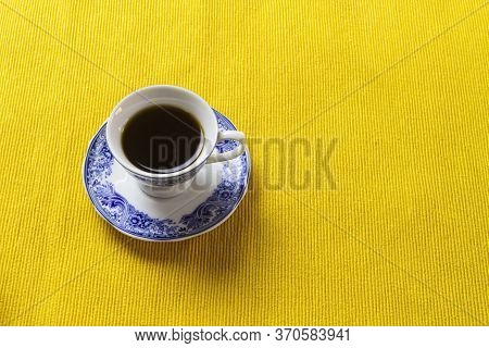 Chinese Porcelain Coffee Cup On Top Of Yellow Placemat.