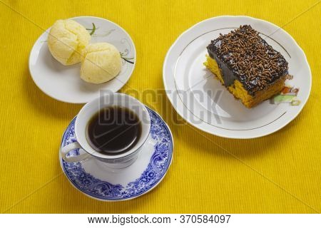 Carrot Cake Icing Chocolate, Brazilian Cheese Bread And Coffee Cup And On The Yellow Placemat.