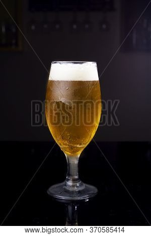 Ice Cold Glass Full Of Beer, With Chopp Pilsen On A Dark Background In A Pub