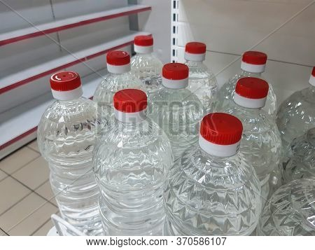 Perspective View Of Goods Shelf With Water Bottles And On Background Empty Shelves In The Supermarke