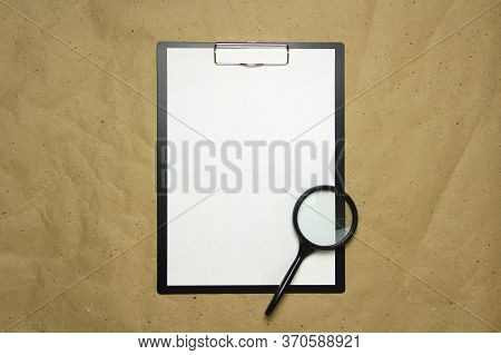 A Tablet With A White Sheet Of A4 Format With Magnifier On A Beige Craft Paper. Concept Of Analysis,