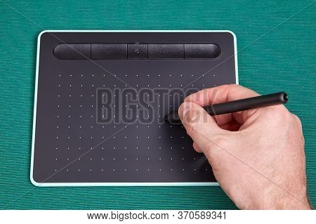 The Artist's Hand Holds A Stylus, Or Pen Over The Screen Of A Graphic Tablet, This Is An Input Devic