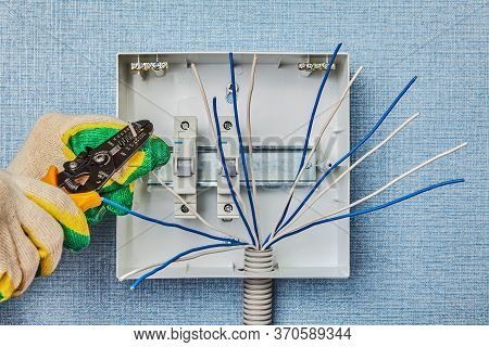 An Electrician Removes Insulation From The End Of A Copper Wire Using A Stripper Cutter. Installatio