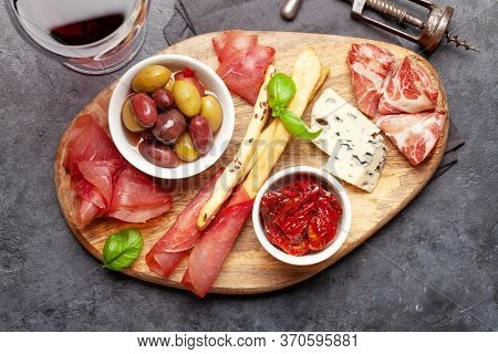 Cheese, meat and olives antipasto. Appetizer selection on wooden board. Top view. Flat lay
